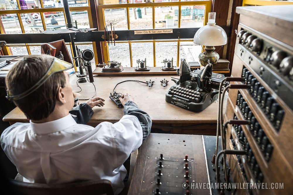 A mannequin of a telegraph operator sits at a desk surrounded by historic communication equipment at the Colorado Railroad Museum in Golden, Colorado.