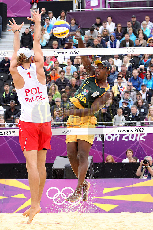 Freedom Chiya of South Africa shoots but Mariusz Prudel of Poland blocks during the preliminary phase - Pool D Beach Volleyball match between Poland and South Africa held at the Horse Guards Parade Stadium in London as part of the London 2012 Olympics on the 1st August 2012..Photo by Ron Gaunt/SPORTZPICS