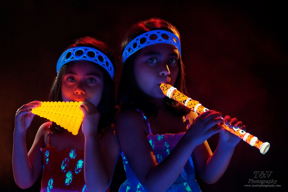 Two young girls with matching glowing outfits play glowing flutes.Black light