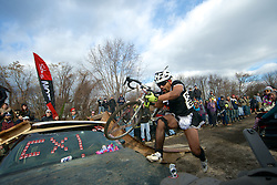 Annual Bilenky Junkyard Cyclocross & SSCXWC '13 Qualifier rounds - North Philadelphia, PA USA - December 7, 2013; A cyclist wearing a maid's costume climbs over the hood of a car, bike in hand.