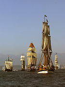 Tall Ships form up to parade in Elliott Bay.  At right center is the Lady Washington, directly behind to the left is the Hawaiian Chieftian, at far right in the distance is the tallest Tall Ship the Europa. (Greg Gilbert / The Seattle Times)