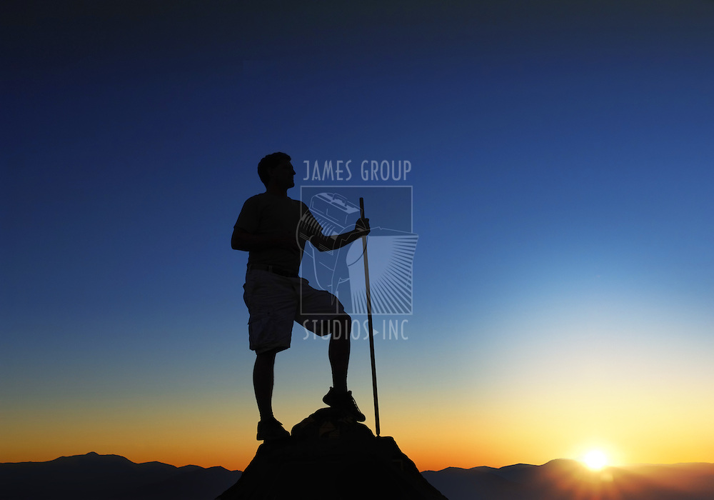 Man at the top of a mountain range at sunrise