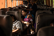 AGUA CALIENTE, HONDURAS - MAY 27, 2014:  A woman with two children rides a bus from San Pedro Sula, Honduras to Guatemala City, Guatemala. The manager of the bus line estimated over 80 percent of this route's passengers are migrants headed north, trying to enter the United States illegally. PHOTO: Meridith Kohut for The New York Times