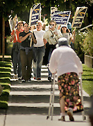 12/26/2004: Pacific Northwest Magazine<br /> Bearing Witness<br /> 2004 Seattle Times Pictures of the Year<br /> <br /> 082304 Striking union employees and their supporters at Group Health Cooperative begin a planned five-day strike, picketing outside the Capitol Hill clinics;  a woman who said she was a patient leaves following her appointment.<br /> <br /> Group Health Cooperative;  nurses, janitors, other union employees begin first day of planned five-day strike.  Hospital and clinics on Capitol Hill.