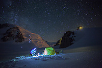 A lone mountaineer, as seen at 3 a.m. preparing the first brew of warm water on a cold Summer night on Col du Midi. In the background groups of climbers venture up the north face of Mont Blanc du Tacul.