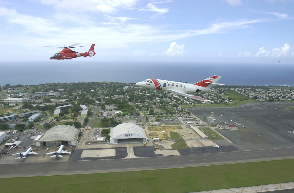 Aerial view of a United States Coast Guard HU-25 Falcon Jet (right), a medium-range surveillance fixed-wing aircraft., and HH-65B helicopter, both stationed at Coast Guard Air Station Borinquen (below) in Puerto Rico. The primary mission of the Station is search and rescue. The surrounding area around the airport was Ramey Air Force Base.  (U.S. Air Force photo/Master Sgt. Lance Cheung)