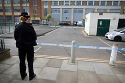 © Licensed to London News Pictures. 02/05/2019. London, UK. A police officer guards another crime scene at Somerford Grove in Hackney near to where a 15 year old boy was stabbed to death last night. A patch of blood can be seen in the road. Scotland Yard say police were called just before 9.00pm.The boy was pronounced dead at the scene at 9.49pm. Photo credit: Peter Macdiarmid/LNP