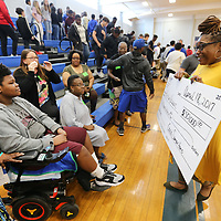 Teetta Vasser walks towards her son Keshun, 12, holding a check for &50,000 that was given to them Wednesday morning at Tupelo Middle School. The money was raised by various fundraisers though the school and Keshun's church, West Jackson Street Baptist Church. Keshun is in need of a wheelchair accessible van and other items around his home to help him with his daily needs after being shot in the neck in September that left him paralyzed from the waist down.