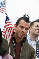 Young man holding American flag, portrait
