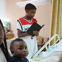 Joshua Gladney, 10, of Tupelo, reads a Bible verse, to Cloteria Cayson, a resident at Tupelo Nursing and Rehab Center on Monday afternoon. Gladney, along with other children, is attending the Red Oak Baptist Church summer reading program and part of a group of children that come to read to the residents of the Nursing and rehab center.