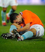 A distressed Robin Van Persie of Netherlands clutches his right ankle as he goes down injured during the friendly match with Italy.