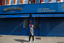 © Licensed to London News Pictures. 21/03/2020. London, UK. A woman wearing a face mask walks past a closed restaurant in Green Lanes, Haringey, north London. The closures follow Prime Minister, BORIS JOHNSON'S request that all restaurants, cafes and pubs should close until further notice as the Coronavirus impact worsens. Photo credit: Dinendra Haria/LNP