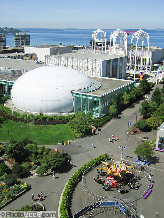 In this 2007 view from the Space Needle's 100-foot SkyLine Level banquet room, see the domed IMAX Theatre and stylistic arches of the Pacific Science Center, at Seattle Center, Washington, USA. Note rides of the Fun Forest Amusement Park (no longer in operation 2011).