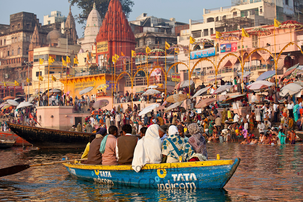 Tourists in boat advertising TATA Indicom on River Ganges at Varanasi, Benares, Northern India