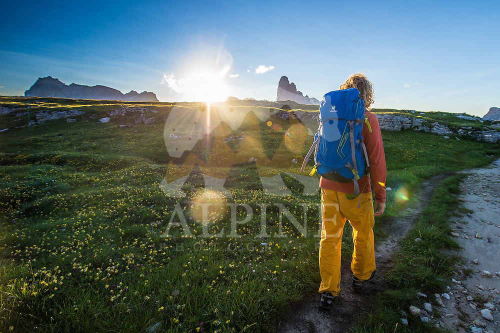 A back view of a male athlete as seen on a cold but sunny Summer morning, hiking on Monte Piana, South Tyrol, Italy.