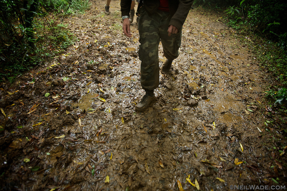 A hiker walks in mud in Yangming Shan National Park in Taipei, Taiwan.