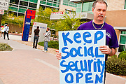 06 APRIL 2011 - PHOENIX, AZ: Harley Hembd (CQ HEMBD) an AFGE member from Luke Air Force Base, pickets the Social Security offices on N 7th Ave in Phoenix Wednesday. A handful of people attended the picket, which was organized by Strengthen Social Security, Alliance for Retired Americans and AFGE (American Federation of Government Employees). The picket was held to draw attention to the importance of Social Security in advance of an expected government shutdown later this week. Similar events were held across the country.   PHOTO BY JACK KURTZ
