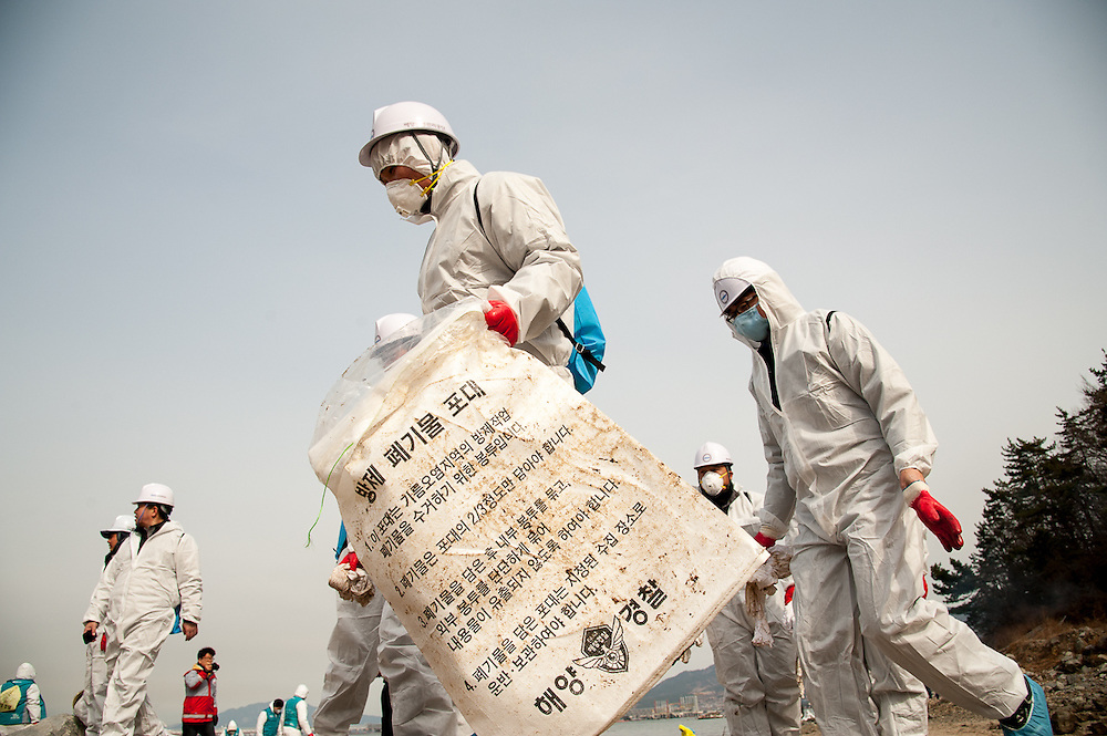 Clean up workers near the site of an oil spill in Yeosu, South Korea.
