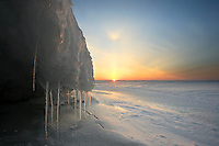 Sunrise illuminates icicles on ice cave in winter on Lake Ontario