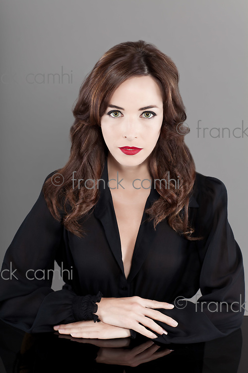 Portrait of a beautiful brunette serious seductress woman in black casual sitting at table isolated on gray background