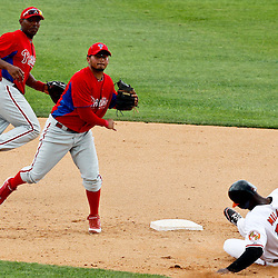 March 20, 2012; Sarasota, FL, USA; Philadelphia Phillies second baseman Freddy Galvis (13) turns a double play with a force out of Baltimore Orioles right fielder Jai Miller (13) during the bottom of the seventh inning of a spring training game at Ed Smith Stadium.  Mandatory Credit: Derick E. Hingle-US PRESSWIRE
