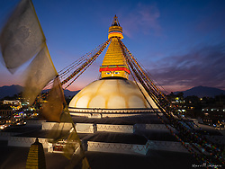 Nepal, Kathmandu, Boudhanath Stupa and prayer flags at sunset