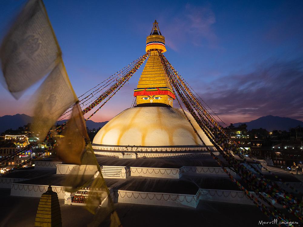 Nepal, Kathmandu, Boudhanath Stupa and prayer flags at sunset