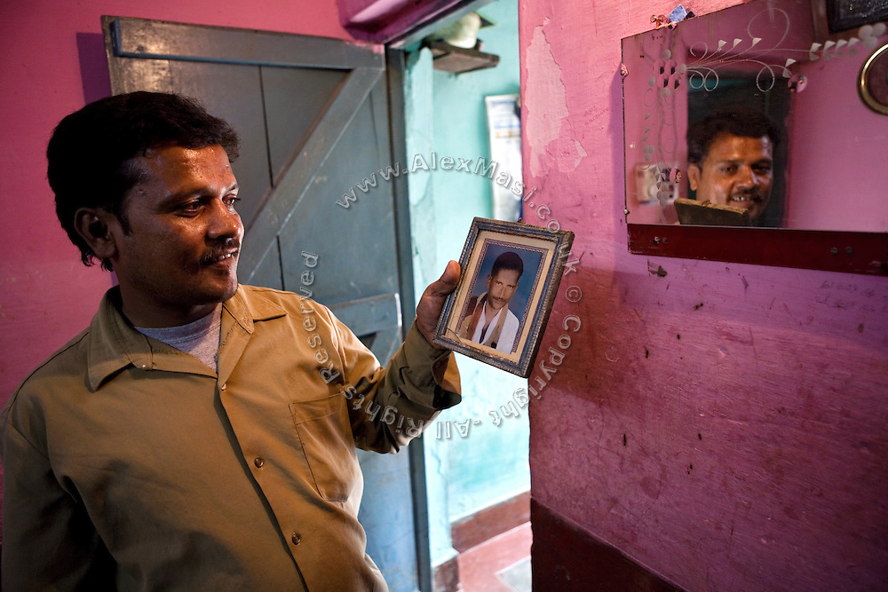 Shafiq Syed, 34, is smiling at the image of his deceased father inside his mother's home in the poor Bangalore neighbourhood where he now lives with his family. Shaifq has been the main character of the Cannes' Camera D'Or 1988 winner Salaam Bombay, but after the movie he failed to become a star, fell back into poverty and lived on the streets for years before he became a rickshaw (tuk-tuk) driver in his home city of Bangalore, Karnataka State, India.
