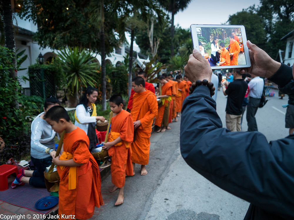 """12 MARCH 2016 - LUANG PRABANG, LAOS:  Tourists photograph Buddhist monks during the morning tak bat in Luang Prabang. Luang Prabang was named a UNESCO World Heritage Site in 1995. The move saved the city's colonial architecture but the explosion of mass tourism has taken a toll on the city's soul. According to one recent study, a small plot of land that sold for $8,000 three years ago now goes for $120,000. Many longtime residents are selling their homes and moving to small developments around the city. The old homes are then converted to guesthouses, restaurants and spas. The city is famous for the morning """"tak bat,"""" or monks' morning alms rounds. Every morning hundreds of Buddhist monks come out before dawn and walk in a silent procession through the city accepting alms from residents. Now, most of the people presenting alms to the monks are tourists, since so many Lao people have moved outside of the city center. About 50,000 people are thought to live in the Luang Prabang area, the city received more than 530,000 tourists in 2014.      PHOTO BY JACK KURTZ"""