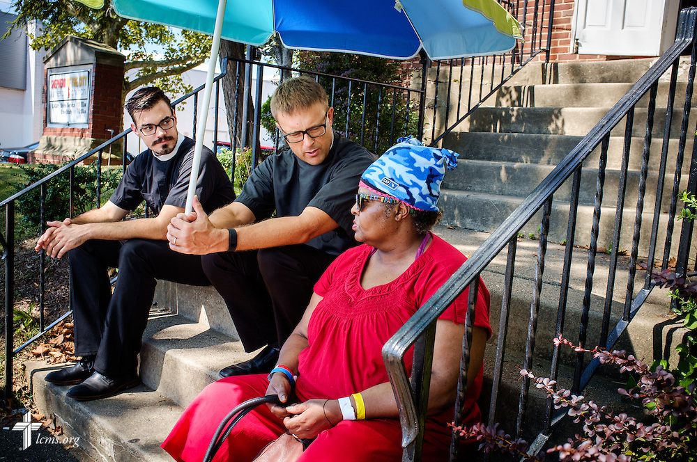 The Rev. Adam DeGroot, national missionary pastor, and Vicar Jacob Benson, talk with Michele Walker, who visited the first domestic Mercy Medical Team on Friday, Aug. 26, 2016, on the steps of Shepherd of the City Lutheran Church in Philadelphia. LCMS Communications/Erik M. Lunsford