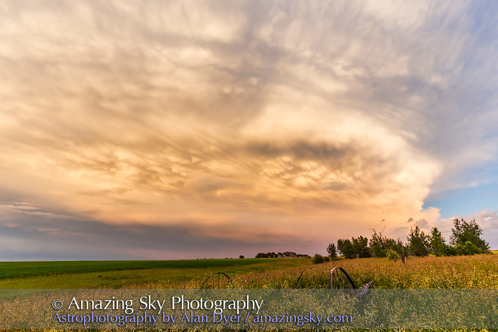 A thunderstorm retreating southeast across the Alberta prairie on July 2, 2016, at sunset under the ideal lighting conditions. The storm shows some mammatiform cloud structures on the underside from downdrafts in the storm. This is part of a 650-frame time-lapse sequence, with the 16-35mm lens and Canon 6D.