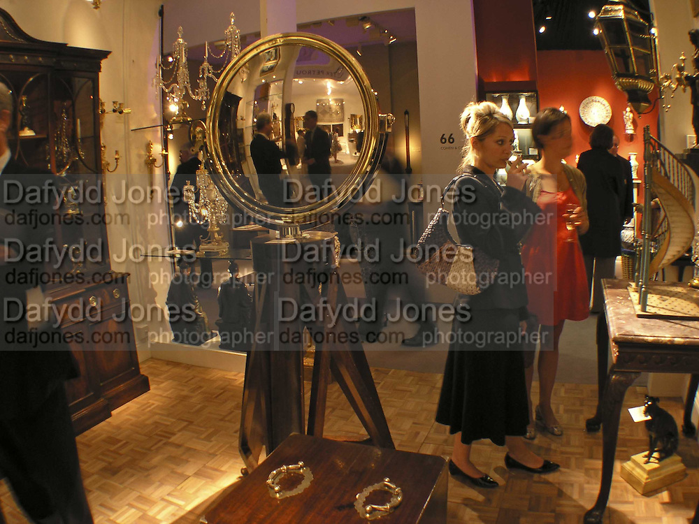 Speculum Metal mirror on 'Jeremy' stand, Vanessa Theos and  Lindsey Dupler, The opening  day of the Grosvenor House Art and Antiques Fair.  Grosvenor House. Park Lane. London. 14 June 2006. ONE TIME USE ONLY - DO NOT ARCHIVE  © Copyright Photograph by Dafydd Jones 66 Stockwell Park Rd. London SW9 0DA Tel 020 7733 0108 www.dafjones.com