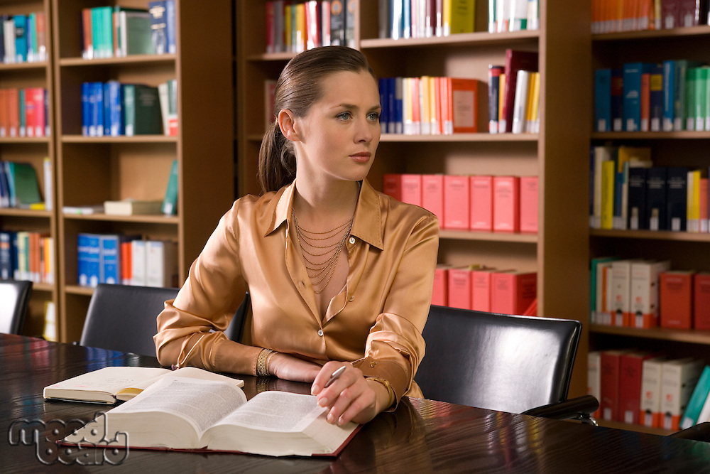 Young woman with book working at desk in library