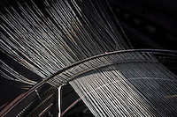 """SOVERIA MANNELLI, ITALY - 17 NOVEMBER 2016: A detail of warps running through an old warping mill is seen here at the Lanificio Leo woolen mill in Soveria Mannelli, Italy, on November 17th 2016.<br /> <br /> Lanificio Leo was the first and last machine-operated woolen mill of Calabria, founded in 1873, it employed 50 people until the 1970s, when national policies to develop Italy's South cut out small businesses and encouraged larger productions or employment in the public administration.<br /> <br /> The woolen mill was on stand-by for about two decades, until Emilio Salvatore Leo, 41, started inviting international designers and artists to summer residencies in Soveria Mannelli. With their inspiration, he tried to envision a future for his mill and his town that was not of a museum of the past,<br /> Over the years, Mr. Leo transformed his family's industrial converter of Calabrian wool into a brand that makes design products for home and wear. His century old machines now weave wool from Australia or New Zealand, cashmere from Nepal and cotton from Egypt or South America. He calls it a """"start-up on scrap metals,"""" referring to the dozens of different looms that his family acquired over the years.<br /> <br /> Soveria Mannelli is a mountain-top village in the southern region of Calabria that counts 3,070 inhabitants. The town was a strategic outpost until the 1970s, when the main artery road from Naples area to Italy's south-western tip, Reggio Calabria went through the town. But once the government started building a motorway miles away, it was cut out from the fastest communications and from the most ambitious plans to develop Italy's South. Instead of despairing, residents benefited of the geographical disadvantage to keep away the mafia infiltrations, and started creating solid businesses thanks to its administrative stability, its forward-thinking mayors and a vibrant entrepreneurship numbering a national, medium-sized publishing house, a leading school furnit"""