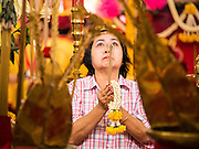 "23 JUNE 2015 - MAHACHAI, SAMUT SAKHON, THAILAND:  A woman prays at the City Pillar Shrine in Mahachai. The Chaopho Lak Mueang Procession (City Pillar Shrine Procession) is a religious festival that takes place in June in front of city hall in Mahachai. The ""Chaopho Lak Mueang"" is  placed on a fishing boat and taken across the Tha Chin River from Talat Maha Chai to Tha Chalom in the area of Wat Suwannaram and then paraded through the community before returning to the temple in Mahachai.  PHOTO BY JACK KURTZ"
