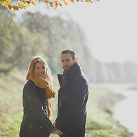 Young adult couple holding hands looking at the camera