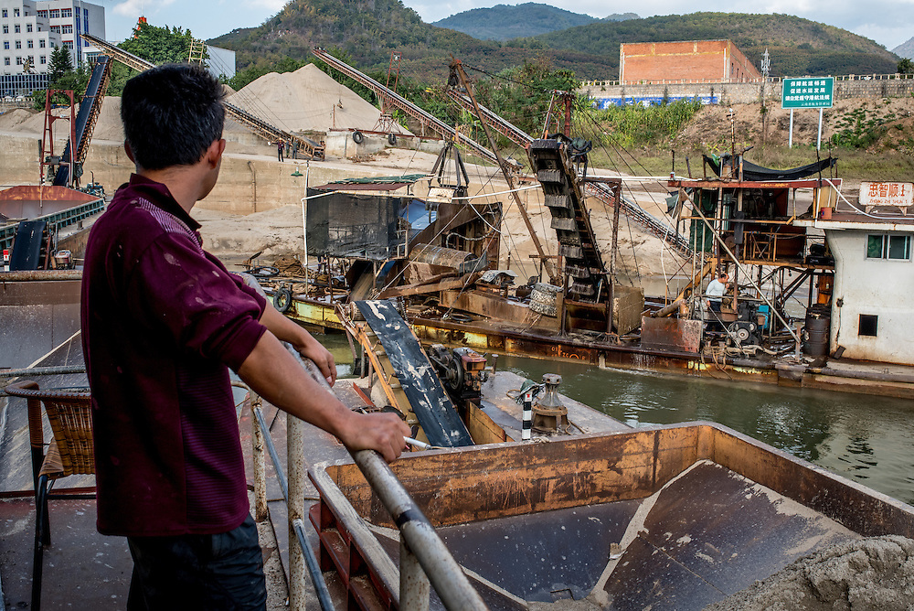 Sand dredgers work along the banks of the Lancang (Mekong) river in Simaogangzhen, Yunan, China. The dredged sand is sold locally and to large scale construction sites in nearby major cities such as Kunming and Jinhong.