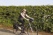 A tourist is cycling on the road towards Burythorpe, Yorkshire, England, United Kingdom.