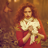 Female youth with curly red hair wearing an orange dress and white scarf standing among the falling autumn leaves.