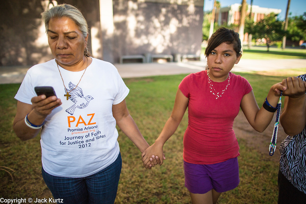 18 JUNE 2012 - PHOENIX, AZ:  PETRA FALCONE (left), from PAZ, checks her smart phone during a prayer to see if the US Supreme Court ruled on SB1070 Monday. About 20 people, members of the immigrant rights' group Promise AZ (PAZ) held a prayer vigil at the Arizona State Capitol in Phoenix Monday praying that the US Supreme Court would overturn SB 1070, Arizona's controversial anti-immigrant law. The court's ruling had been expected Monday, June 18 but the the court said the ruling would not come out until later this month. Members of PAZ said they would continue their vigil until the ruling was issued.   PHOTO BY JACK KURTZ