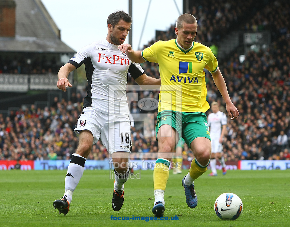 Picture by Paul Chesterton/Focus Images Ltd.  07904 640267.31/03/12.Aaron Hughes of Fulham and Steve Morison of Norwich in action during the Barclays Premier League match at Craven Cottage stadium, London.