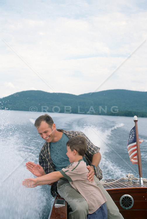 man and child splashing water while on a  motor boat in New Hampshire