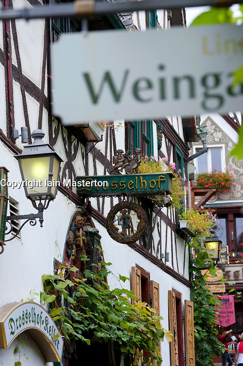 View of signs outside restaurants on famous tourism Drosselgasse Street in popular town of Rudesheim on River Rhine in Germany