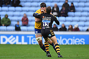 Bath back row Josh Bayliss (7) is tackled by Wasps flyhalf Jimmy Gopperth (12) during the Gallagher Premiership Rugby match between Wasps and Bath Rugby at the Ricoh Arena, Coventry, England on 2 November 2019.