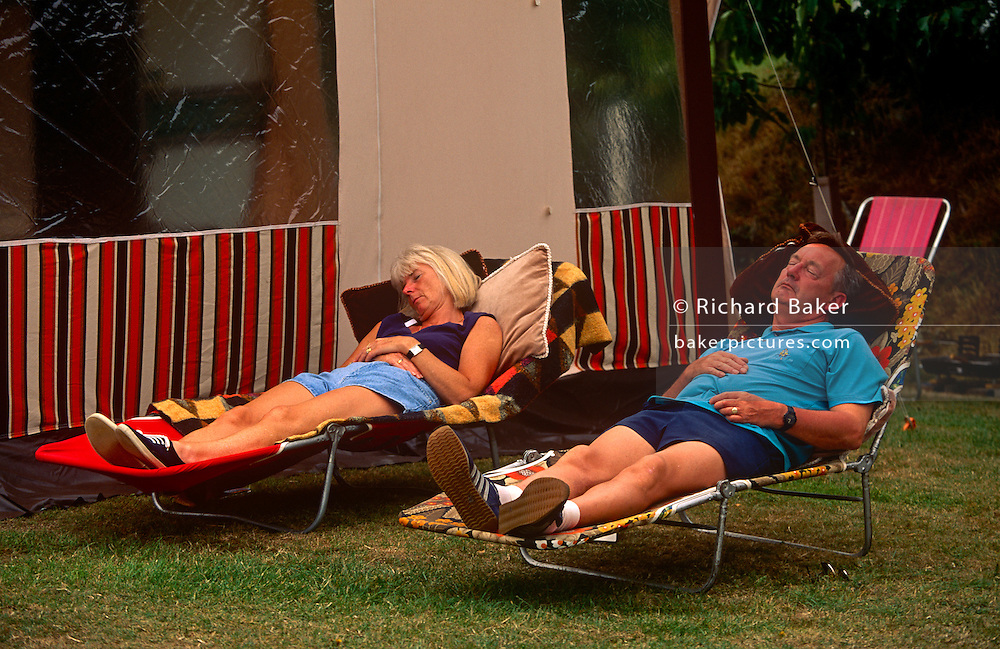 A couple sleep on sun loungers outside the awning of their parked caravan at a caravan site in Devon. Both tired out from a day's touring or walking, the two are sound asleep, dreaming of the peaceful life on holiday in the quiet corner of the otherwise busy location.