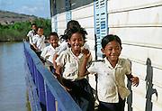 Cambodge, village flottant de Chong Khneas. Les villages flottants du Cambodge, construits autour du grand lac Tonle Sap doivent leurs noms au fait que les maisons sont ba?ties sur des flotteurs et se de?placent au gre? des saisons se?ches et humides. Ici, les enfants jouaient en courant sur la passerelle ceinturant l'e?cole flottante.