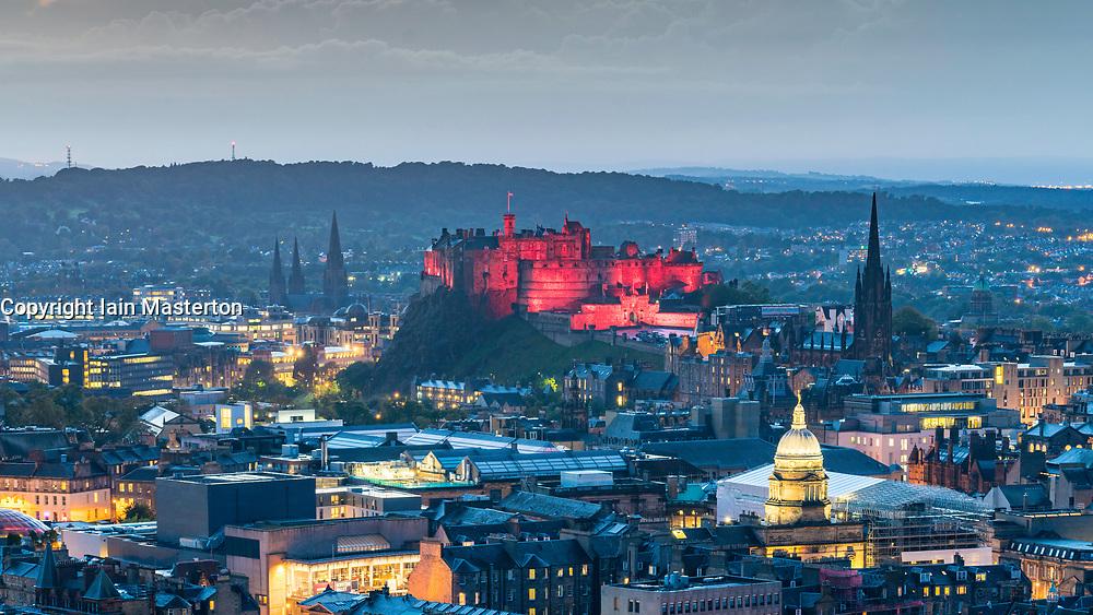 Evening view of Edinburgh Castle illuminated in red and skyline of city from Salisbury Crags, Edinburgh, Scotland, United Kingdom.