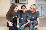 ICS volunteers Olivia Smith, Sregmao Khleg & Alice Munday sit on the steps of the local school in the village of Banteay Char, near Battambang, Cambodia.