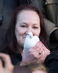 © London News Pictures. 11/01/2014. London, UK. Pamela Duggan, mother of Mark Duggan, holding a white dove before releasing at at the vigil.  The family of Mark Duggan attend a vigil outside Tottenham Police Station in London, following a Coroners ruling of a lawful killing in the case of Mark Duggan earlier this week. Mark Duggan was hot dead by police in an incident that sparked riots across London and England.  Photo credit: Ben Cawthra/LNP