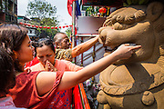 """10 FEBRUARY 2013 - BANGKOK, THAILAND:  People pray for a prosperous New Year on Chinese New Year at the lions guarding the entrance to Wat Mangkon Kamalawat, the largest Chinese temple in Bangkok. It is customary for people to rub some cash or their wallets and pocketbooks on the lion's face and in its mouth during the prayers. Bangkok has a large Chinese emigrant population, most of whom settled in Thailand in the 18th and 19th centuries. Chinese, or Lunar, New Year is celebrated with fireworks and parades in Chinese communities throughout Thailand. The coming year will be the """"Year of the Snake"""" in the Chinese zodiac.   PHOTO BY JACK KURTZ"""